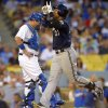 Milwaukee Brewers\' Carlos Gomez, right, scores on his solo home run, as Los Angeles Dodgers catcher A.J. Ellis waits during the sixth inning of a baseball game, Saturday, Aug. 16, 2014, in Los Angeles. (AP Photo/Mark J. Terrill)