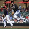 Photo - Colorado Rockies shortstop Troy Tulowitzki, right, throws Los Angeles Angels' Ian Stewart out at first as third baseman Nolan Arenado looks on during the first inning of a spring training baseball game in Scottsdale, Ariz., Friday, March 7, 2014. (AP Photo/Chris Carlson)
