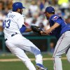 Texas Rangers pitcher Martin Perez, right, tags out Los Angeles Dodgers\' Scott Van Slyke on a grounder during the third inning of an exhibition baseball game in Glendale, Ariz., Friday, March 7, 2014. (AP Photo/Paul Sancya)