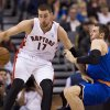 Photo - Toronto Raptors forward Jonas Valanciunas (17) knocks down New York Knicks forward Andrea Bargnani, right, during first half NBA pre-season basketball action in Toronto on Tuesday, Oct. 21, 2013. (AP Photo/The Canadian Press, Nathan Denette)