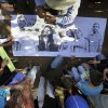 "In this Nov. 15, 2012 photo, farmers prepare a banner with pictures of landless farmers, some of whom were arrested during clashes with police, as they prepare to march to demand their release at the Yvy Pyta settlement near Curuguaty, Paraguay. The ""Massacre of Curuguaty"" on June 15 killed 11 farmers and 6 police officers when negotiations between farmers occupying a rich politician\'s land ended with a barrage of bullets. The underlying dispute that set up the clash was decades in the making. The area\'s poor residents have long alleged that the land was effectively stolen from the state by Sen. Blas Riquelme, a leader of the Colorado Party that backed dictator Alfredo Stroessner from 1954 to 1989, and has dominated the nation\'s politics ever since. (AP Photo/Jorge Saenz)"