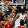 Photo - Sacramento Kings forward Rudy Gay (8) scores around Houston Rockets point guard Aaron Brooks (0) and Rockets forward Greg Smith, back left, during the first half of an NBA basketball game in Sacramento, Calif., Sunday, Dec. 15, 2013. (AP Photo/Genevieve Ross)