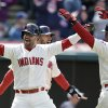 Photo - Cleveland Indians' Nick Swisher, left, and Nyjer Morgan, right, celebrate after scoring on a three-run double by Jason Kipnis off Minnesota Twins starting pitcher Ricky Nolasco in the fourth inning of a baseball game on Sunday, April 6, 2014, in Cleveland. Indians' Mike Aviles also scored. (AP Photo/Tony Dejak)