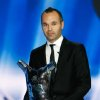 Photo -   The best soccer player of the year FC Barcelone's Spanish midfielder, Andres Iniesta, holds his trophy during the UEFA Champions League draw, at the Grimaldi Forum, in Monaco, Thursday, Aug. 30, 2012. (AP Photo/Claude Paris)