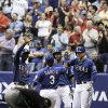 Texas Rangers\' Leury Garcia (3) is congratulated on a run by Rangers\' Jurickson Profar, left, Jim Adduci, right, and Julio Borbon during an exhibition baseball game against the San Diego Padres, Saturday, March 30, 2013, at the Alamodome in San Antonio. (AP Photo/Darren Abate)