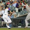 Photo - Colorado Rockies first baseman Justin Morneau tries to tag out Cincinnati Reds Billy Hamilton in the first inning of a baseball game on Thursday, Aug. 14, 2014, in Denver. Hamilton was out at first base. (AP Photo/Chris Schneider)