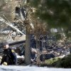 Photo - A police officer walks near the debris after an explosion at a townhouse complex Tuesday, March. 4, 2014, in Ewing, N.J. A hospital says it is receiving at least six patients from the explosion in a suburb of New Jersey's capital city that caused heavy damage. (AP Photo/Mel Evans)