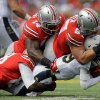 Photo - Ohio State defensive lineman Steve Miller, from left, linebacker Curtis Grant and defensive lineman Joey Bosa sack Navy quarterback Keenan Reynolds in the first half of an NCAA college football game in Baltimore, Saturday, Aug. 30, 2014. (AP Photo/Patrick Semansky)