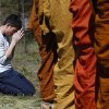 Adisorn Gronski, left, prays while monks from the Atammayatarama Buddhist Monastery in Woodinville chant for victims of the deadly mudslide in Oso, Wash., Tuesday, April 1, 2014, near a road block in Oso. The March 22 mudslide destroyed the rural mountainside community northeast of Seattle. (AP Photo/The Herald, Sofia Jaramillo) MANDATORY CREDIT.
