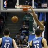 Photo - Milwaukee Bucks' Giannis Antetokounmpo dunks against Minnesota Timberwolves' Kevin Love (42) and Kevin Martin (23) during the first half of an NBA basketball game, Saturday, Dec. 28, 2013, in Milwaukee. (AP Photo/Jeffrey Phelps)