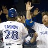 Photo -   Toronto Blue Jays welcome Colby Rasmus as he returns to the dugout after scoring against the Boston Red Sox during the third inning of a baseball game in Toronto on Monday, April 9, 2012. (AP Photo/The Canadian Press, Frank Gunn)