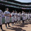 New York Yankees players stand for the national anthem in throw-back uniforms prior to a baseball game against the Boston Red Sox at Fenway Park in Boston, Friday, April 20, 2012, during a celebration of the 100th anniversary of the first regular-season game at the ball park. (AP Photo/Elise Amendola)