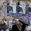 Egyptians chat under defaced posters of Presidential candidate Ahmed Shafiq for the upcoming elections in Cairo, Egypt, Thursday, April 26, 2012. Egypt\'s election commission announced the final list of candidates this week for next month\'s presidential elections. Arabic on the posters read,
