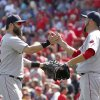 Photo - Boston Red Sox' Mike Napoli, left, and pitcher Edward Mujica congratulate each other after the Red Sox beat the Cincinnati Reds 5-4 in a baseball game, Wednesday, Aug. 13, 2014, in Cincinnati.  (AP Photo/David Kohl)