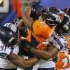 Denver Broncos running back Knowshon Moreno (27) is tackled by Seattle Seahawks defensive end Chris Clemons (91) and defensive end Cliff Avril (56) during the first half of the NFL Super Bowl XLVIII football game Sunday, Feb. 2, 2014, in East Rutherford, N.J. (AP Photo/Matt York)