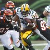 Green Bay Packers running back Cedric Benson (32) is tackled by Cincinnati Bengals defensive end Michael Johnson (93) and defensive tackle Geno Atkins (97) during the first half of an NFL preseason football game, Thursday, Aug. 23, 2012, in Cincinnati. (AP Photo/John Grieshop)