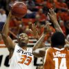 Oklahoma State\'s Marcus Smart (33) shoots between Texas\' Jonathan Holmes (10) and Texas\' Julien Lewis (14) during a men\'s college basketball game between Oklahoma State University (OSU) and the University of Texas at Gallagher-Iba Arena in Stillwater, Okla., Saturday, March 2, 2013. Photo by Nate Billings, The Oklahoman
