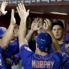 Photo - New York Mets' Daniel Murphy (28) gets high-fives from teammates in the dugout after he scored a run against the Arizona Diamondbacks during the third inning of a baseball game on Monday, April 14, 2014, in Phoenix. (AP Photo/Ross D. Franklin)