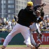 Pittsburgh Pirates\' Travis Snider, left, takes down Milwaukee Brewers\' Carlos Gomez during a skirmish between the teams during the third inning of a baseball game in Pittsburgh, Sunday, April 20, 2014. Gomez and Snider were ejected from the game. (AP Photo/Gene J. Puskar)