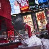 Workers clean snow from the steps of TKTS Times Square ticket booth, Thursday, Jan. 2, 2014, in New York. The storm is expected to bring snow, stiff winds and punishing cold into the Northeast. (AP Photo/John Minchillo)