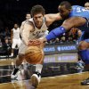 Photo - Brooklyn Nets center Brook Lopez (11) and Orlando Magic forward Glen Davis (11) go after a loose ball in the first half of their NBA basketball game at Barclays Center, Monday, Jan. 28, 2013, in New York. (AP Photo/Kathy Willens)