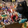 """SURPRISE REUNION / MILITARY FATHER: U.S. Chad Chudoba, wearing a panther mascot costume, reads a book to kindergarten students. His son, Isaac, who doesn\'t know his dad is inside the costume, is seated on the floor, fourth face from the left, in the front row. Army Sgt. Chad Chudoba arrived at Del City Elementary School Monday morning, Sep. 30, 2013, to see his five-year-old son for the first time in more than nine months. Before reuniting with his son, Sgt. Chudoba disguised himself as the school\'s mascot, stepping into a full-body panther costume and reading a book to his son, Isaac\'s kindergarten classmates who had assembled on the floor of the school\'s library for story time. When he finished the story, Sgt. Chudoba rose from the small chair and removed the head of the mascot and told the giggling kindergarteners he wasn\'t really a panther, and proudly announced, """"I am Isaac\'s daddy."""" Then, he extended his arm toward the boy wearing rolled-up jeans and a western style, pearl-snap shirt near the front of the group, and clasped his son\'s small hand into his as he pulled the boy onto his lap and hugged him. Chudoba is a member of the Army\'s 1245th transportation company and returned Saturday after serving with his unit in Afghanistan for 9 months. After the reunion, the younger Chudoba admitted he thought the voice of the panther sounded much like his dad\'s, but the biggest clue for the kindergartener that this was no ordinary mascot were its hands. He told his dad he recognized his hands as he listened to the story and watched the mascot turn the pages of the book. Photo by Jim Beckel, The Oklahoman."""