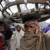 Indian porters walk in a market area on a cold winter morning in Kolkata, India, Friday, Jan. 11, 2013. More than 100 people have died of exposure as several parts of India deal with historically cold temperatures. (AP Photo/Bikas Das)