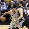 Photo - San Antonio Spurs' Tim Duncan, left, drives around Memphis Grizzlies' Marc Gasol, of Spain, during the second half of Game 1 of the Western Conference final NBA basketball playoff series Sunday, May 19, 2013, in San Antonio. (AP Photo/Darren Abate)