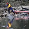 A searcher steps off of his boat to look through debris following a deadly mudslide, Tuesday, March 25, 2014, in Oso, Wash. At least 14 people were killed in the 1-square-mile slide that hit in a rural area about 55 miles northeast of Seattle on Saturday. Several people also were critically injured, and homes were destroyed. (AP Photo/Elaine Thompson)
