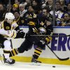 Photo - Boston Bruins'  Dougie Hamilton (27) checks Buffalo Sabres' Zemgus Girgensons (28) during the first period of an NHL hockey game in Buffalo, N.Y., Wednesday, Feb. 26, 2014. (AP Photo/Gary Wiepert)