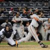 Photo - Baltimore Orioles' Nick Markakis follows through on an RBI single as New York Yankees catcher Brian McCann watches during the ninth inning of a baseball game Wednesday, April 9, 2014, at Yankee Stadium in New York. The Orioles won 5-4. (AP Photo/Bill Kostroun)