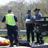 In a Sunday, April 1, 2012 photo, authorities remove victims at the scene of a deadly crash , near Williamsburg, Kan. Police said a box truck, which had living quarters inside, was pulling a trailer when it crashed into a ravine after it hit a guardrail and a concrete bridge, killing 5 of the 18 people were inside the vehicle. A family friend said a Minnesota family and some friends were taking a spring break vacation to see a motocross race. (AP Photo/The Ottawa Herald, Jeanny Sharp) NO SALES