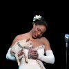 "Photo - This photo provided by Jeffrey Richards Associates shows Audra McDonald as Billie Holiday in ""Lady Day at Emerson's Bar & Grill""  while holding Roxie. This Broadway season has been rich with roles for African-Americans and audiences are responding, from the packed Brooks Atkinson Theatre, where the musical ""After Midnight"" celebrates Duke Ellington's years at the Cotton Club, to the standing-room only Circle in the Square, where Audra McDonald is channeling Billie Holiday.  (AP Photo/Jeffrey Richards Associates, Evgenia Eliseeva)"