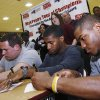 Members of the Jenks high school football team including Garrett Patterson (left), Brandon Waggoner, Trey\'vonne Barre, and Braden Calip sign up for their new college teams, taken during signing Day in Jenks, Okla., on February 6,2013. JAMES GIBBARD/Tulsa World