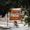 Photo -   In this Monday, July 16, 2012, photo, a bicyclist passes in front of a billboard for Coca Cola outside a restaurant in Atlanta. The Coca-Cola Co. says its net income slipped in the second quarter from a year ago, as rising costs for ingredients offset its expansion overseas. The world's biggest beverage maker, which makes Minute Maid, Powerade and Dasani, says revenue growth was powered by higher prices in the U.S. and expansion in emerging markets such as India, where volume rose 20 percent. (AP Photo/David Goldman)