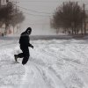 A man runs through blowing snow as he makes his way through deep snow crossing Sheridan in Bricktown Tuesday afternoon. A severe winter storm created whiteout conditions and caused snow drifts that made problems for the few motorists who ventured out Tuesday afternoon, Feb. 1, 2011. Photo by Jim Beckel, The Oklahoman