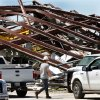 A worker who was part of a crew that worked Saturday afternoon, June 1, 2013, to remove equipment from this large storage building walks past mangled steel in this heavily damaged supply yard for Cactus Drilling Company on State Highway 66 in El Reno on Saturday, June 1, 2013. Employee David Stottemyre was working in the lot when the tornado took aim at the plant. Stottemyre ran inside the large supply storage building and took shelter as the tornado passed over, leaving the building in a twisted pile of steel and metal. He was not injured. Photo by Jim Beckel, The Oklahoman.
