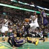 Indiana Pacers small forward Paul George (24) falls to the floor as Boston Celtics point guard Rajon Rondo (9) passes in the lane against the defense of Pacers\' Roy Hibbert (55) during the second half of an NBA basketball game, Saturday, March 1, 2014, in Boston. (AP Photo/Mary Schwalm)