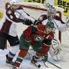 Colorado Avalanche\'s Erik Johnson, left, tries to push Minnesota Wild\'s Zach Parise out of the way as Avalanche goalie Semyon Varlamov of Russia defends the net in the first period of an NHL hockey game Saturday, Jan. 19, 2013 in St. Paul, Minn. Parise and Ryan Suter signed identical 13-year, $98 million contracts with the WIld. (AP Photo/Jim Mone)