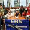 Enid High School Plainsmen, seated from elft, Logan Miller, Seth Handley and Lance Smith, receive congratulations from their teammates during national signing day at the EHS Library, Wednesday, Feb. 6, 2013, in Enid, Okla. (AP Photo/Enid News and Eagle, Bonnie Vculek)