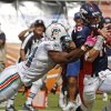 Photo -   Miami Dolphins outside linebacker Cameron Wake (91) tackles Denver Broncos quarterback Tim Tebow (15) during the first half of an NFL football game Sunday, Oct. 23, 2011, in Miami. (AP Photo/Hans Deryk)