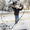 Photo - Scott Springer, an engineer with the North Little Rock Electric Department moves a fallen power line away from the street on Lakeview Road in North Little Rock on Wednesday, Dec. 26, 2012. Spotters were out assessing where downed lines were so crews could make line repairs easier.  Much of North Little Rock saw more than nine inches of snow on Christmas day. (AP Photo/Arkansas Democrat-Gazette, Karen E. Segrave)