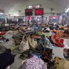 Passengers rest as they wait for the arrival of a train at a railway station in Allahabad, India, Saturday, Dec. 29, 2012. North India continues to face extreme weather conditions with dense fog affecting flights and trains, according to local reports. (AP Photo/Rajesh Kumar Singh)