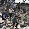 Syrian inspectors investigate the crater in front of a damaged military intelligence building where two bombs exploded, at Qazaz neighborhood in Damascus, Syria, on Thursday May 10, 2012. Two strong explosions ripped through the Syrian capital Thursday, killing or wounding dozens of people and leaving scenes of carnage in the streets in an assault against a center of government power. (AP Photo/Bassem Tellawi) ORG XMIT: BEI120