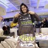 Julie Keim, of Mukilteo, Wash., looks toward a clerk to check on sizing as she purchases a stack of Seattle Seahawks\' Super Bowl championship shirts and caps at the team store, Monday, Feb. 3, 2014, in Seattle. The Seahawks defeated the Denver Broncos on Sunday in the Super Bowl XLVIII NFL football game, 43-8. (AP Photo/Elaine Thompson)