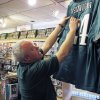 Andy Hageman, owner of the House of Football in Albuquerque, N.M. shows why the authentic NFL jerseys in his store can be compared to fakes by comparing the jerseys\' quality, Thursday, Jan. 31, 2013. Hageman said that authentic NFL jerseys do not have cardboard behind the numbers. Federal officials announced Thursday that investigators have confiscated more than $13.6 million worth of phony sports merchandise nationwide over the past five months and expect to seize more in New Orleans during Super Bowl week. Homeland Security Investigation officials said that Mexican drug cartels are getting involved in the NFL black market. (AP Photo/Russell Contreras)
