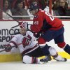 Photo - Washington Capitals defenseman Dmitry Orlov, right, hits New Jersey Devils right wing Michael Ryder during the first period of an NHL hockey game on Saturday, Feb. 8, 2014, in Washington. (AP Photo/ Evan Vucci)
