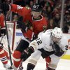 Photo - Anaheim Ducks' Mathieu Perreault (22) controls the puck against Chicago Blackhawks' Michal Handzus (26) during the first period of an NHL hockey game in Chicago, Friday, Jan. 17, 2014. (AP Photo/Nam Y. Huh)