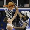 Photo - Orlando Magic's Kyle O'Quinn, right, dunks as he gets past Detroit Pistons' Jonas Jerebko during the first half of an NBA basketball game in Orlando, Fla., Wednesday, Feb. 5, 2014. (AP Photo/John Raoux)