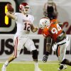 Photo - OU's Landry Jones, left, passes under pressure from Miami's Eric Moncur during action earlier this season. Photo by Nate Billings, The Oklahoman